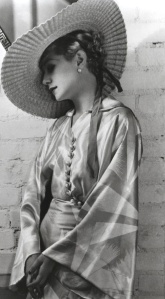 Lilyan is contemplative in a satin robe and wide-brimmed hat.